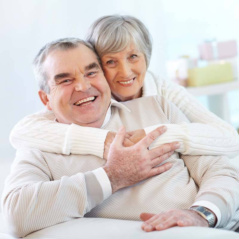 Portrait of a happy senior woman embracing her husband and both looking at camera